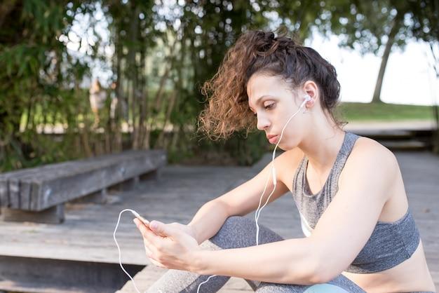 공원에서 음악을 듣고 스포티 한 여자의 근접 촬영