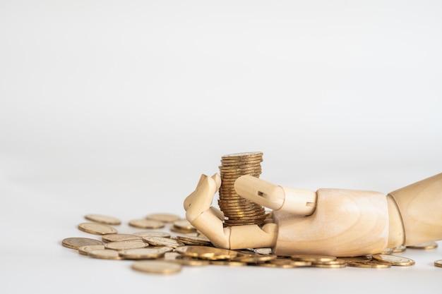 Крупный план стога золотых монет на деревянной руке с кучей монет на белом фоне.