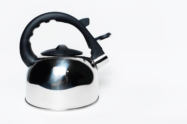 흰색 배경에 고립 된 검은 손잡이와 철강 광택 주전자의 근접 촬영.