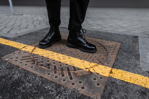 通りの鉄のヴィンテージマンホールの男性の脚にスタイリッシュな革の黒いブーツのクローズアップ。トレンディな靴を履いたトレンディな若者が街を歩きます。モダンなユースカジュアルスタイル。男性のためのファッショナブルな靴
