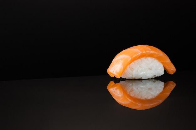 Крупным планом суши с рисом на черном фоне с отражением