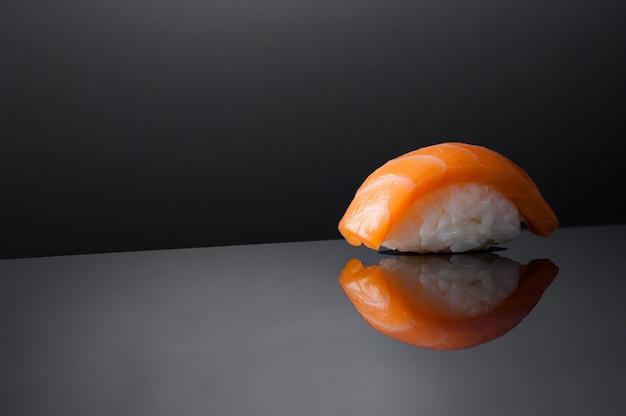 Крупным планом суши с рисом на сером фоне с отражением