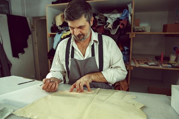 伝統的なアトリエスタジオで服のパターンを作る男性の手で仕立て屋のテーブルのクローズアップ。女性の職業の男。男女共同参画の概念