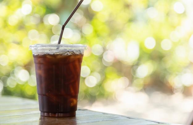 緑の自然の背景を持つ木製のテーブルにアイスブラックコーヒーアメリカーノの持ち帰り用プラスチックカップのクローズアップ。