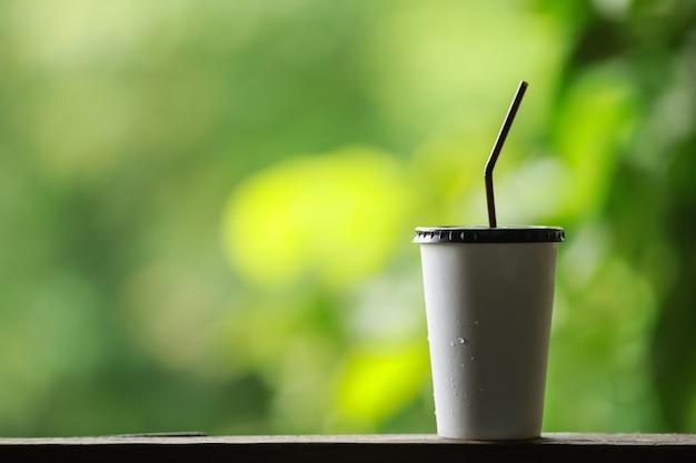 Крупным планом бумажный стаканчик со льдом с пластиковой крышкой и соломинкой на вынос