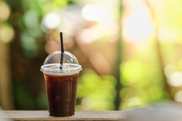 コピースペースを木製のテーブルにアイスブラックコーヒーアメリカーノのテイクアウトプラスチックカップのクローズアップ。