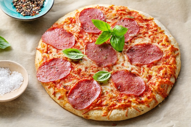 치즈와 향신료와 함께 맛 있는 식욕을 돋 우는 살라미 소시지 피자의 근접 촬영.