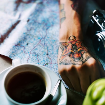 Closeup of tattoo hand with map and coffee cup