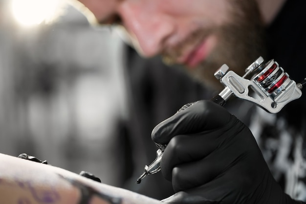 Крупный план татуировщика рисует на бедре женщины