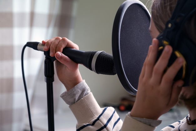 ホームスタジオで音楽を録音するティーンエイジャーのクローズアップ。ヘッドフォンとマイクの録音曲を持つ少女