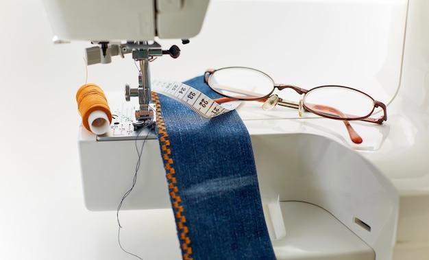 Крупным планом текстильные очки на швейной машине дома