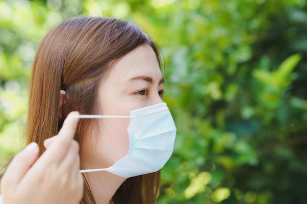 自然なぼかしの背景とマスクの側面図を身に着けているタイの女性のクローズアップ
