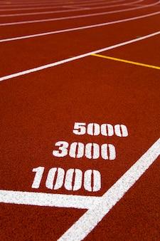 Крупным планом отметки 1000, 3000 и 5000 метров на красной беговой дорожке стадиона