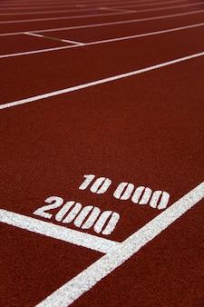 ランニングトラックの2000および10000メートルマークのクローズアップ