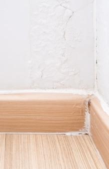 居間の隅にある壊れたフローリングスカートのクローズアップ、雨の湿気のために壁のペンキがはがれました。コピースペースのある正面図。