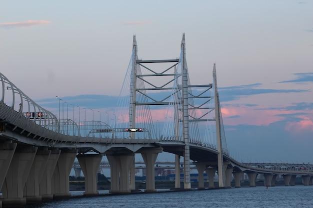アウトバーンの看板に止まらない夕日からの赤い反射で夕方の空を背景に湾の上のケーブル橋と高速道路のクローズアップ