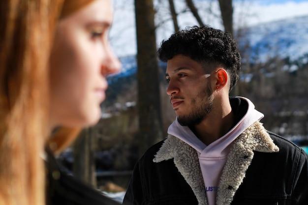 冬の前景で彼のパートナーの顔を横に見ているラテン系の男の顔のクローズアップ