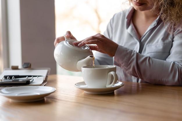 お茶を注ぐ少女の手のクローズアップ。カフェで朝食。