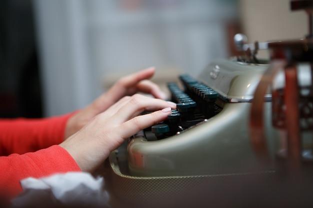 Крупным планом руки человека, печатающего на старой пишущей машинке