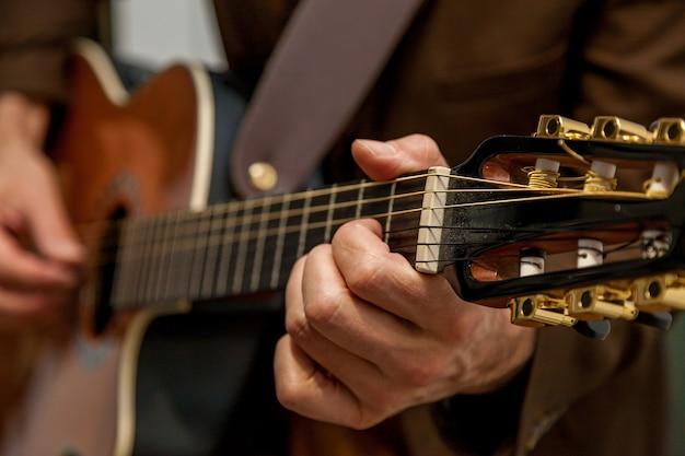 기타를 연주하는 음악가의 손을 닫아 음악가의 손가락을 누르고 있다