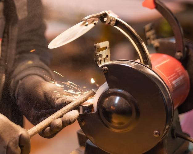 Крупным планом руки работника в черных перчатках, работающего над металлической деталью на красном шлифовальном станке