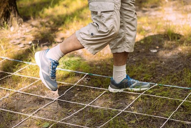 Крупным планом ноги человека, который бежит по лабиринту сетки препятствий на траве тимбилдинг