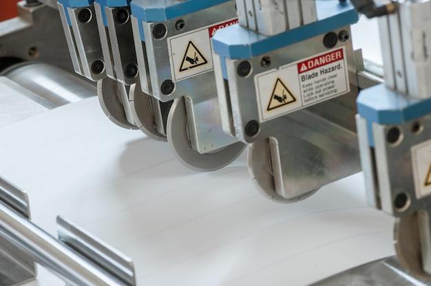 기계 및 장비의 근접 촬영은 자동차 필터용 펠트 직물을 절단하고 고랑으로 만듭니다.