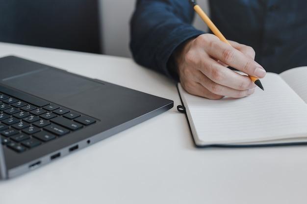 손가락 사이 연필을 잡고 메모장에 쓰는 사람의 손의 근접 촬영.