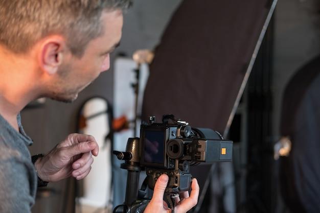Крупным планом фотографа в фотостудии, вид сбоку