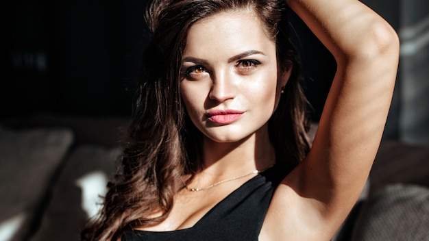 美しいメイクと豪華なセクシーな唇を持つブルネットの魅惑的な顔のクローズアップ