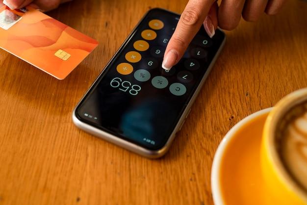 Крупным планом женщина платит и делает покупки с помощью кредитной карты и калькулятора мобильного смартфона