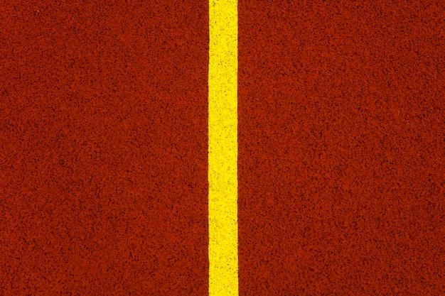 Крупным планом желтая линия на красной беговой дорожке стадиона