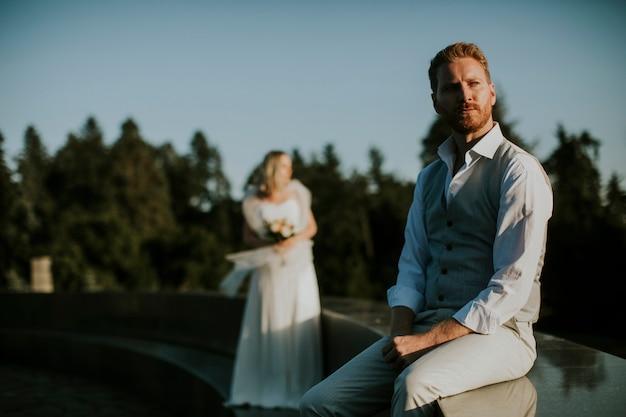 Крупным планом молодой человек молодоженов сидит перед своей молодой невестой