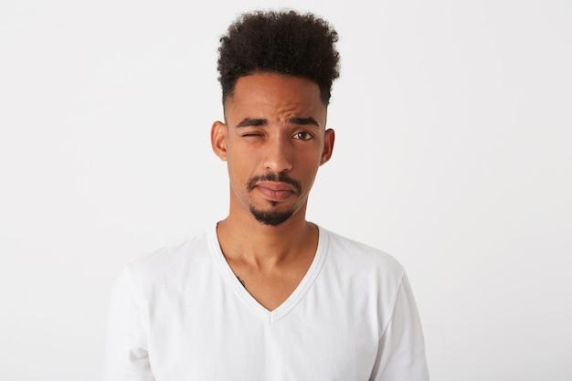 곱슬 머리와 주근깨를 가진 사려 깊은 매력적인 젊은 남자의 근접 촬영은 티셔츠를 입고 잠겨있는 모습과 흰 벽에 고립 된 생각을 옆으로 보이는