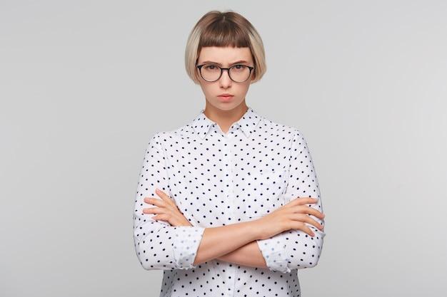 Крупным планом задумчивая довольно блондинка молодая женщина носит рубашку в горошек