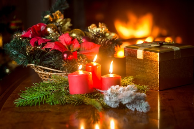 ギフトボックスと装飾的な花輪の横にあるテーブルの上の3つの燃えるクリスマスキャンドルのクローズアップ