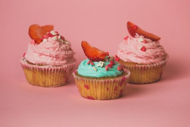 Крупным планом три кексы с клубникой на розовом фоне