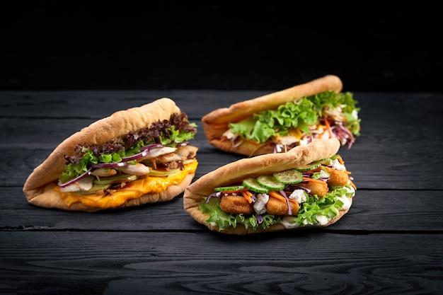 黒い木の表面の3つの異なる食欲をそそるサンドイッチハンバーガーのクローズアップ