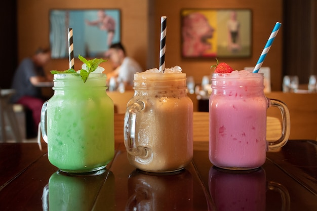 カフェで木製のテーブルに3つの異なる風味のおいしいタイミルクティーのクローズアップ