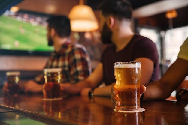 Крупным планом трое молодых людей пьют пиво в баре и смотрят футбольный матч