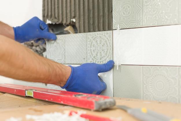Крупный план руки плиточника кладя керамическую плитку на стену в кухню, реновацию