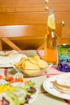 나초 한 그릇, 치킨 파히타 한 접시, 토르티야, 신선한 샐러드, 신선한 맥주와 함께 테이블에 전통적인 멕시코 음식의 클로즈업
