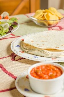 토르티야 한 접시, 신선한 샐러드, 나초, 매운 소스 한 그릇과 함께 테이블에 전통적인 멕시코 음식의 클로즈업