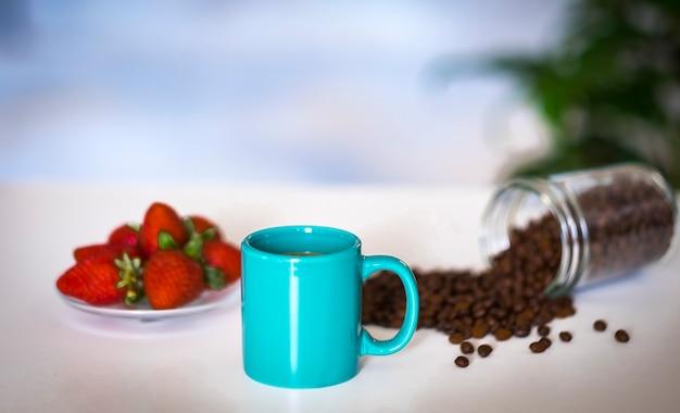 白いテーブルの上のターコイズセラミックコーヒーカップの焦点がぼけたコーヒー豆のクローズアップ