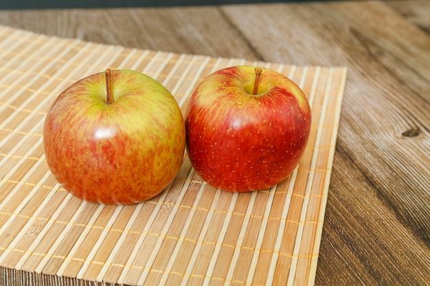 Крупным планом два яблока, с деревянной циновкой, на столе.