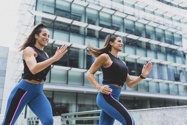 두 명의 매력적인 여성이 달리고 운동을 하는 모습 - 피트니스와 스포츠의 개념