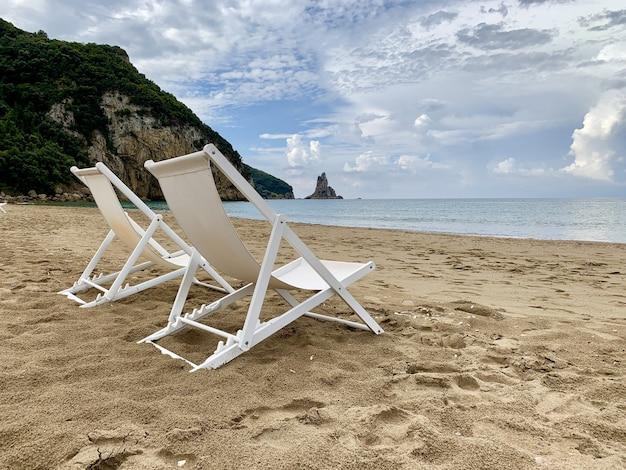 낮 동안 바다 근처 모래 해변에 두 개의 갑판 의자의 근접 촬영