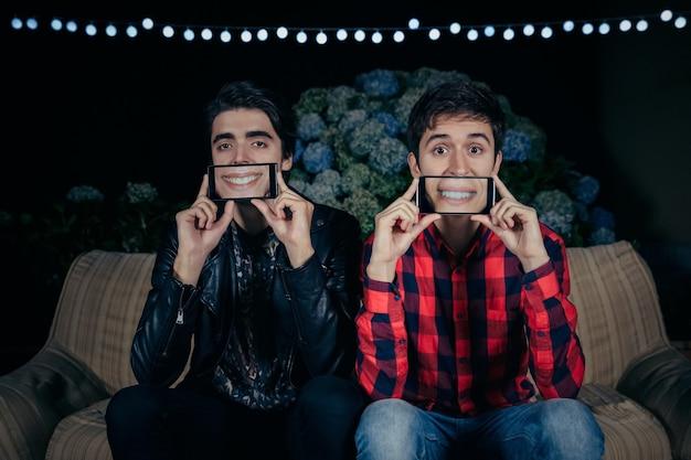 야외 파티 화면에서 웃는 여성의 입을 보여주는 얼굴 위에 스마트폰을 들고 있는 두 명의 재미있는 젊은 남성의 클로즈업. 우정과 축하 개념입니다.