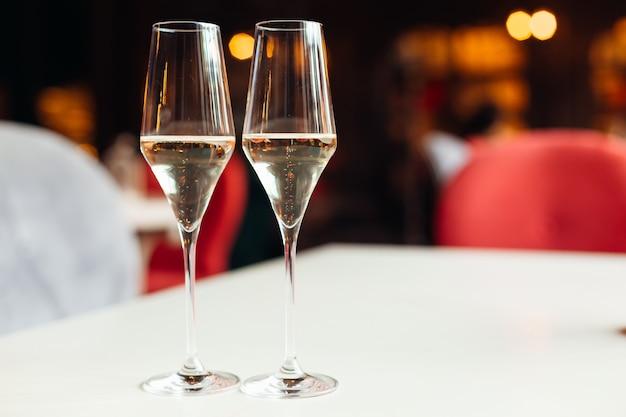 Крупным планом два бокала с шампанским на столе с белой тканью и пузырями