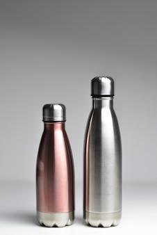 コピースペースで灰色の背景に分離された2つの再利用可能なスチールサーモウォーターボトルのクローズアップ